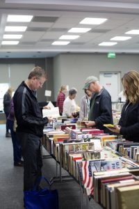 Patrons browsing books at a book sale