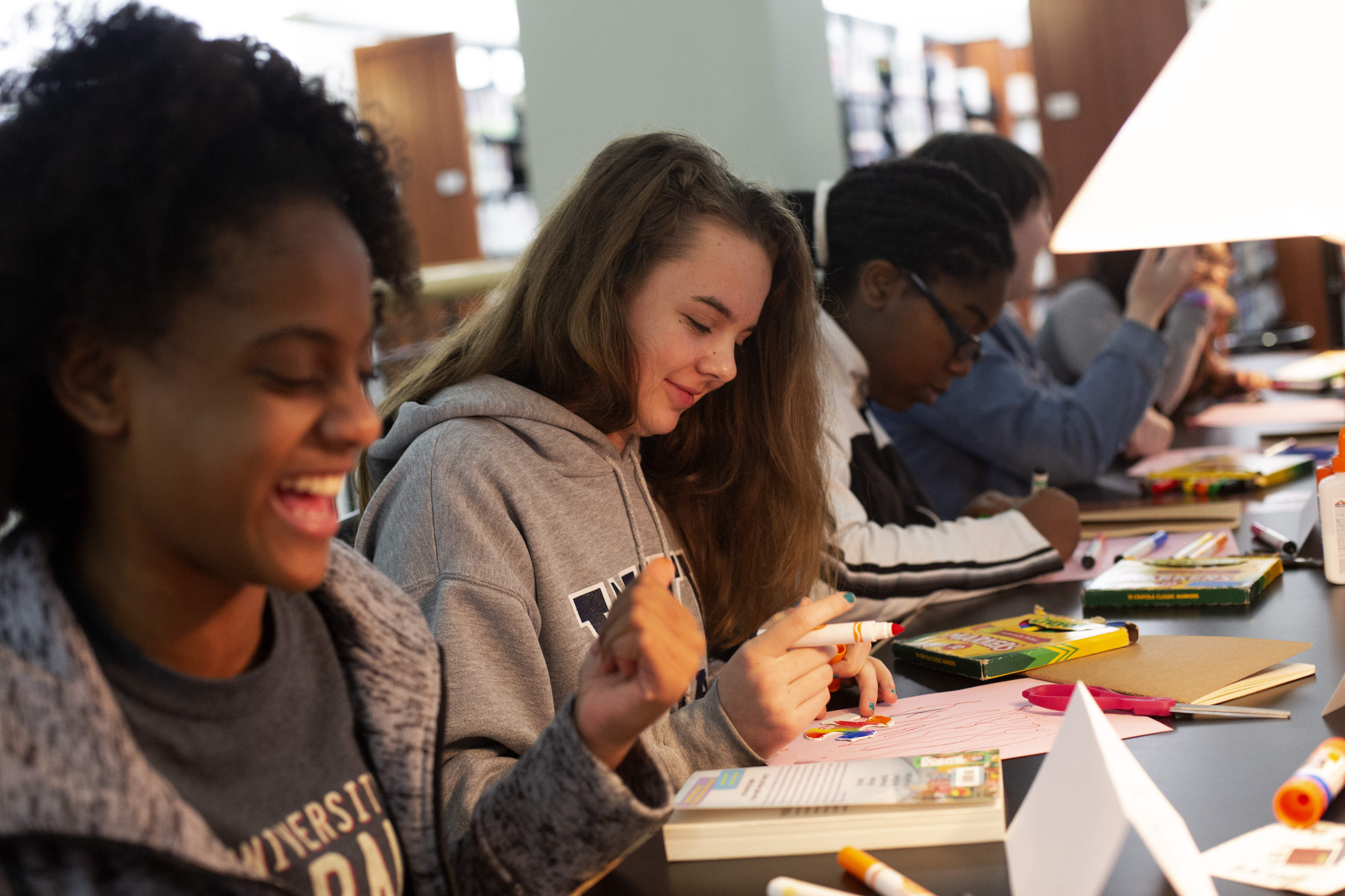 Teens laugh and color at a craft event.