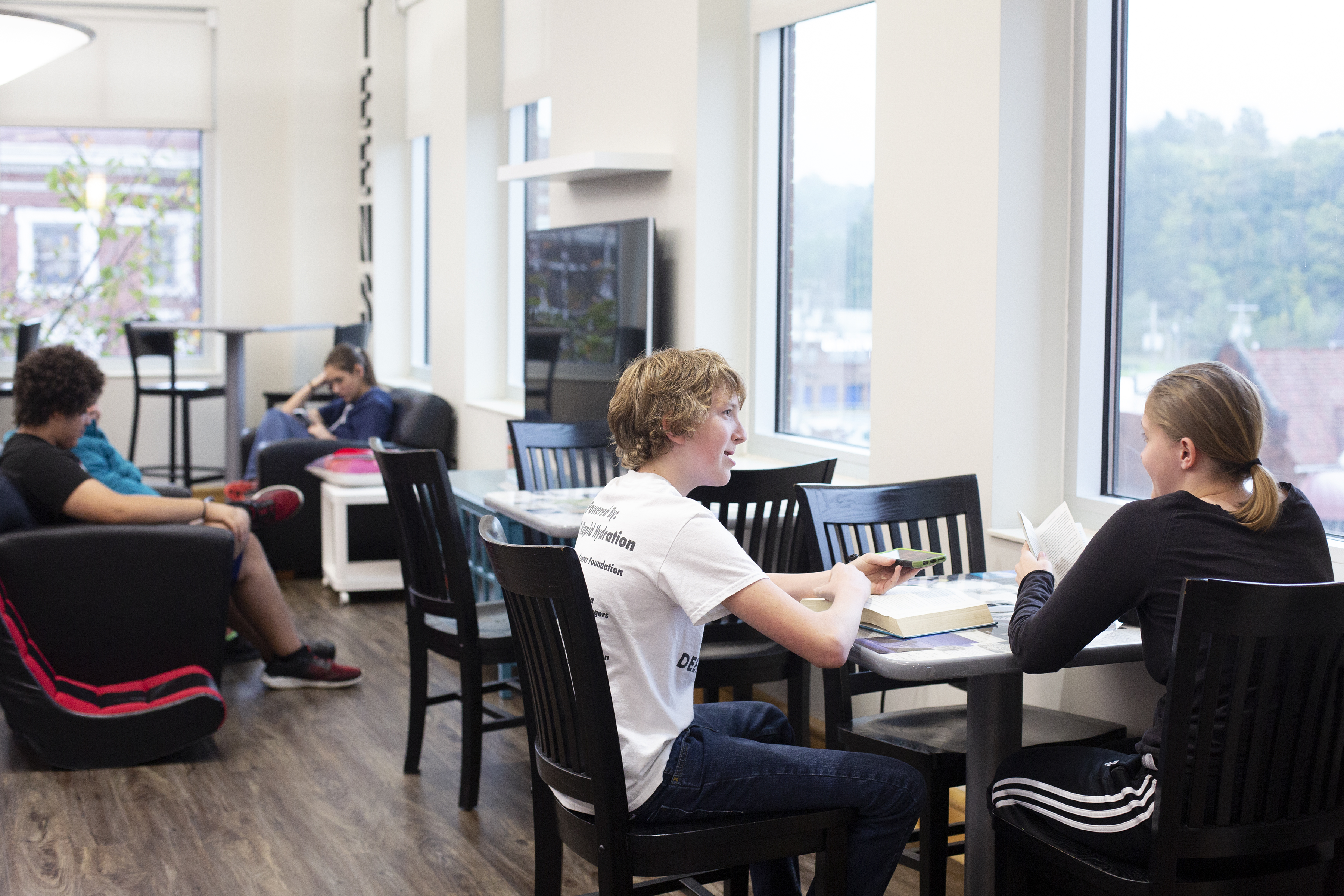 Teens sit at tables and on a sofa in the teen area