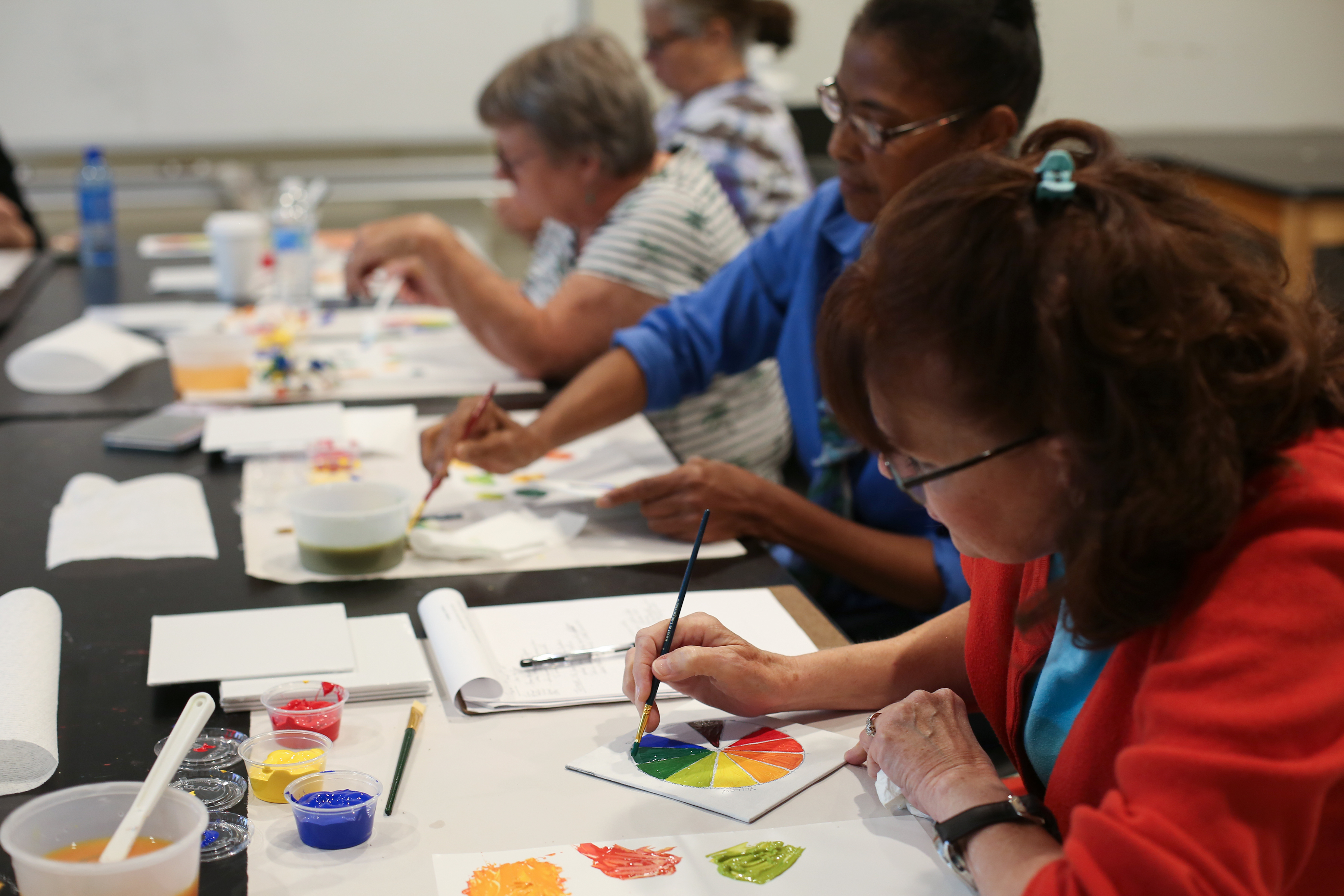 Adults paint swatches at a program organized by JCPL Adult Services