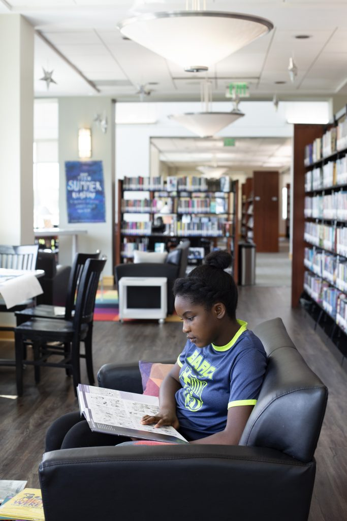 A girl sits and reads on a sofa in the library teen area