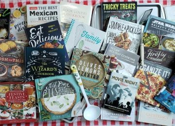 An assortment of cookbooks litter a checkered tablecloth in the latest online book display