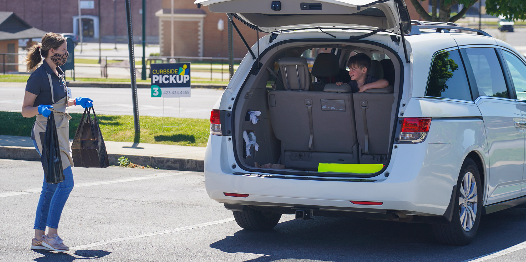 Library Director Julia Turpin puts curbside orders into the back of a car. A child smiles from the back seat.