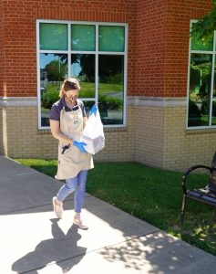 Library Director Julia Turpin helps out as a runner for the library's curbside service