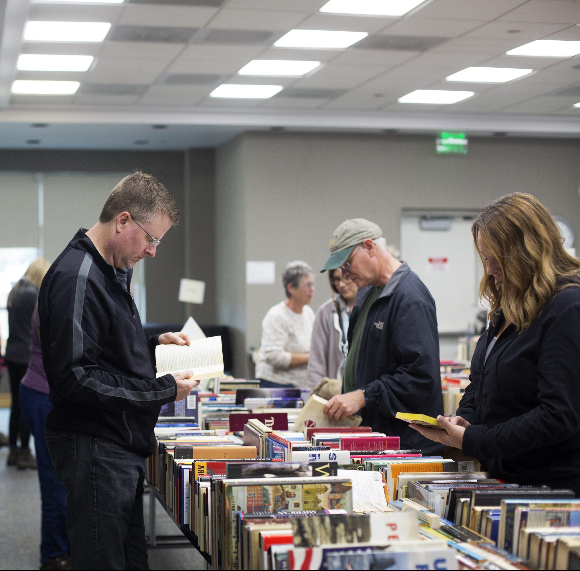 Patrons browse books at a book sale hosted by friends of the library