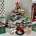 Books about the holidays are creatively arranged into a Christmas tree structure for this months book display