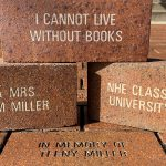 "Three engraved bricks are stacked on top of a layer of other bricks. They feature engravings such as""I cannot live without books"" and ""Dr. & Mrs. John M Miller."""
