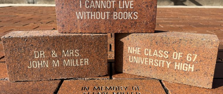"""Three engraved bricks are stacked on top of a layer of other bricks. They feature engravings such as""""I cannot live without books"""" and """"Dr. & Mrs. John M Miller."""""""