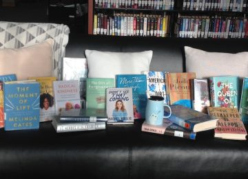 An array of books are laid out on a comfy black couch for the online book display