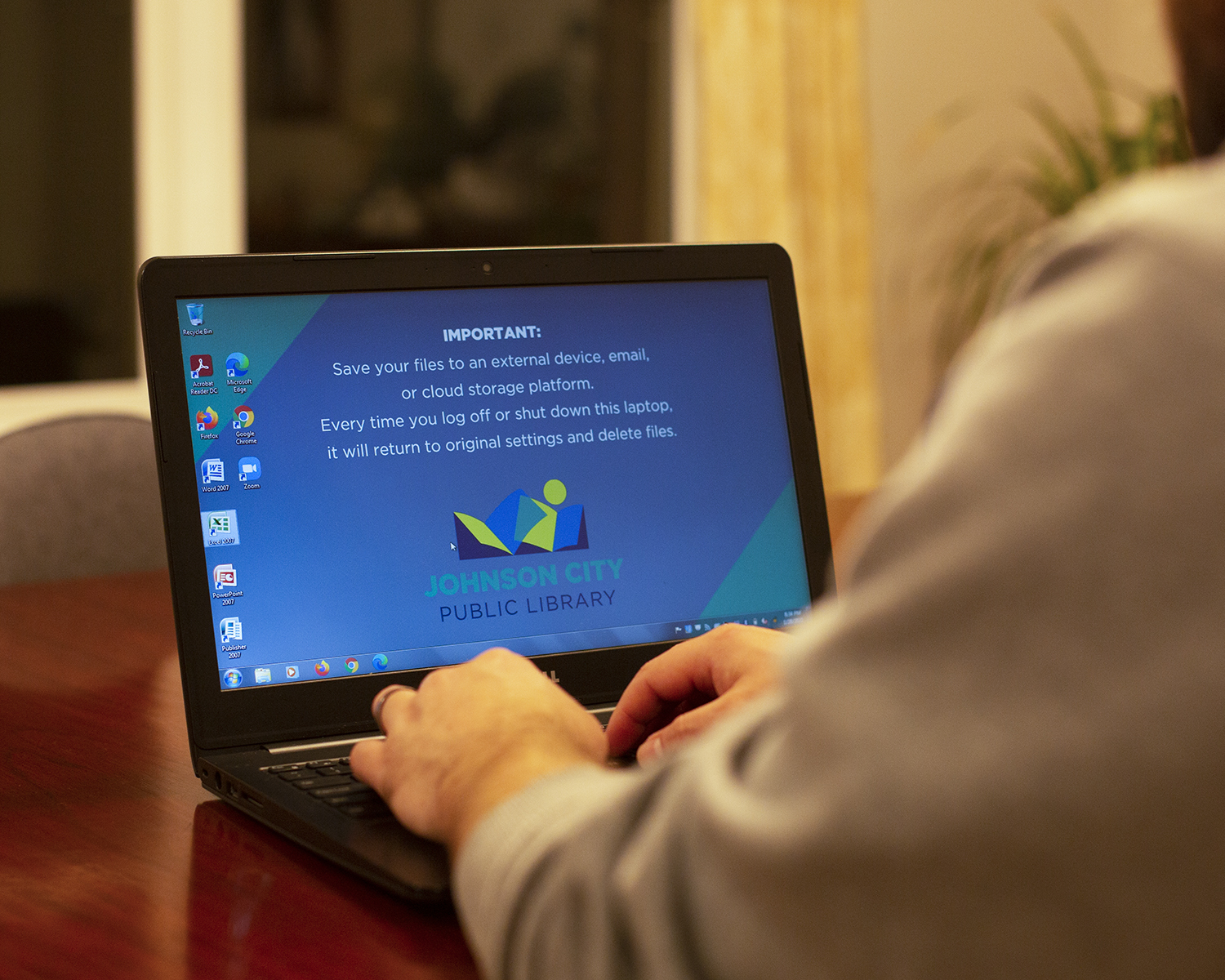 A patron sits at one of the Library's laptops at their home.